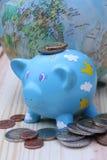Piggy Querneigung und Münzen Lizenzfreie Stockfotos