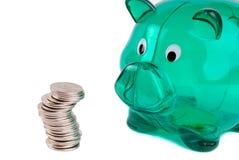 Piggy Querneigung und Münzen Stockfotografie