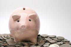 Piggy Querneigung und Münzen lizenzfreie stockbilder