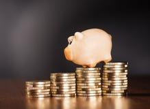 Piggy Querneigung und Münzen Lizenzfreie Stockfotografie