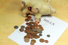 Piggy Querneigung und Rechnungen. Lizenzfreie Stockfotografie