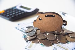 Piggy räddning för symbol som förläggas på högen av pengar - begreppet sparar pengar Arkivfoto