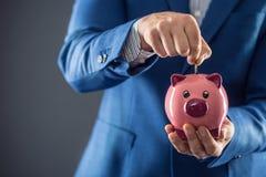 piggy sättande sparande för grupppengar Piggy för affärsman hållande rosa och sättande mynt in i spargrisen Arkivbilder