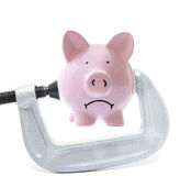 Piggy squeeze. Sad piggy bank being squeezed in a vice, on white Stock Photo