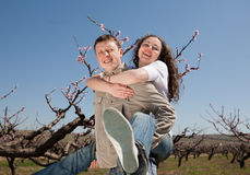 Piggyback. Attractive couple playing in garden among the blossoming peach trees Stock Images