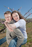 Piggyback. Attractive couple playing in garden among the blossoming peach trees Stock Photo