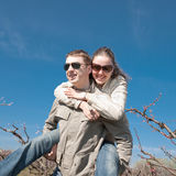 Piggyback. Attractive couple playing in garden among the blossoming peach trees Royalty Free Stock Photo