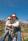 Piggyback. Attractive couple playing in garden among the blossoming peach trees Royalty Free Stock Image