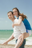 Piggyback. Young men and women playing at the sea Royalty Free Stock Photo