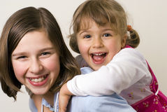 Piggyback. Two happy sisters playing, pigg Stock Photography