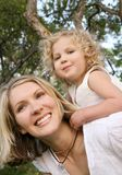 Piggyback. Young attractive mother playing with her daughter outdoors Royalty Free Stock Images