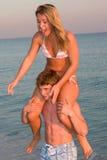 Piggyback. A young man gives a bikini clad woman a piggyback ride at sunset on the beach Royalty Free Stock Photos