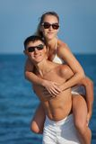 Piggyback. Attractive couple at the sea. Guy carrying on shoulders his girl at seashore in day time Royalty Free Stock Image