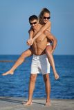 Piggyback. Attractive couple at the sea. Guy carrying on shoulders his girl at seashore in day time Stock Photo