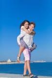 piggyback Bärande flicka för ung man längs sjösida arkivfoto