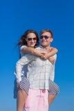 piggyback Bärande flicka för ung man på hans baksida royaltyfria foton