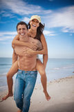 Piggyback at beach Stock Photos