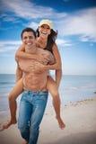 Piggyback at beach. Man carrying woman on a beach, both smiling Stock Photos