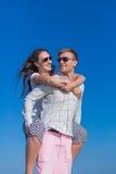 piggyback Individuo que continúa a su muchacha trasera contra el cielo imagen de archivo libre de regalías