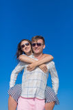 piggyback Muchacha que lleva del hombre joven contra el cielo claro fotografía de archivo