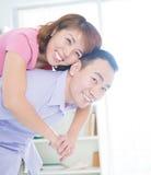Piggyback ride. Asian couple doing a piggyback ride indoor Stock Image