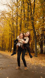 Piggyback ride in autumn forest. Young female giving her friend piggyback ride in autumn forest Royalty Free Stock Photography