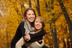 Piggyback ride in autumn forest. Young female giving her friend piggyback ride in autumn forest Stock Images