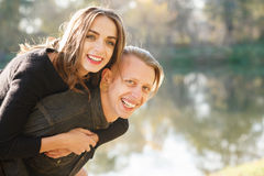 Piggyback ride close-up. Young male giving female piggyback ride outdoors hug Royalty Free Stock Photography