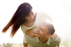 Piggyback ride. Couple in love on a date, young men carrying piggyback his beautiful girlfriend, happy laughing, having fun together Stock Photos