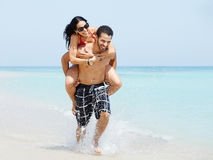 Piggyback ride with happy man and woman. Happy maried adult couple having fun and playing on the sea shore in cuba. Horizontal shape, full length, copy space Stock Image