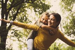 Piggyback ride. Happy single mother. Mother giving her daughter piggyback ride. Carrying on shoulders. Single mother with daughter Royalty Free Stock Photography