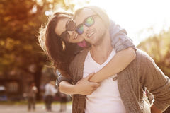 Piggyback ride. Young couple have fun in sunny day Royalty Free Stock Images