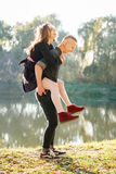 Piggyback ride. Young male giving female piggyback ride outdoors fun Royalty Free Stock Photo