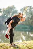 Piggyback ride. Young male giving female piggyback ride outdoors fun Royalty Free Stock Photography
