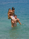 Piggyback in sea. Happy families enjoy in spending summer holidays in Dalmatia (Croatia). The father carried on your shoulders is a son s daughter, (piggy back) Royalty Free Stock Images