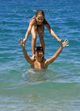 Piggyback at sea. Portrait of a brother and sister in summer party at sea. Sister standing on the shoulders (piggy back) of her brother in crystal clear blue Stock Photos