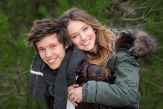 Piggyback teens. Happy smiling teen couple in piggyback in winter clothing Royalty Free Stock Photos