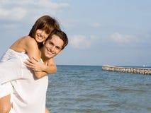 Piggyback vacation fun. Young couple having piggyback fun on vacation Stock Image