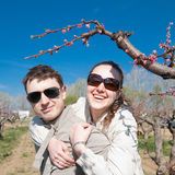 Piggyback. Young man and woman outdoors. Attractive couple playing in garden among the blossoming peach trees Stock Photography