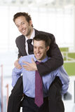 Piggybacking. Young smiling businessman piggybacking his colleague Royalty Free Stock Image