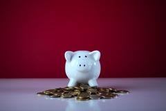 Piggybank über einigen Münzen Stockbild