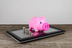 Piggybank και σειρά των χρημάτων νομισμάτων στην ταμπλέτα Στοκ Εικόνες