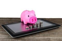 Piggybank και σειρά των χρημάτων νομισμάτων στην ταμπλέτα Στοκ εικόνες με δικαίωμα ελεύθερης χρήσης