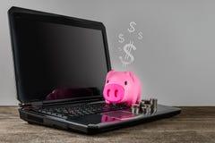 Piggybank και σειρά των χρημάτων νομισμάτων στο πληκτρολόγιο lap-top Στοκ εικόνα με δικαίωμα ελεύθερης χρήσης