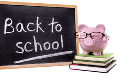 Piggybank πίσω στην υπενθύμιση σχολικών μηνυμάτων, έννοια σχολικών αμοιβών, που απομονώνεται Στοκ Φωτογραφία
