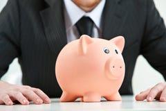 Piggybank στο πρώτο πλάνο σε ένα υπόβαθρο επιχειρηματιών Στοκ Εικόνα