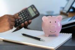 piggybank и калькулятор на калькуляторе co делового документа стола стоковая фотография