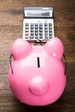 Piggybank с калькулятором на таблице Стоковая Фотография