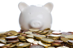 Piggybank. A Piggybank is standing behind some coins Royalty Free Stock Image