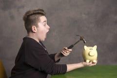 Piggybank abierto del adolescente con el martillo Foto de archivo libre de regalías